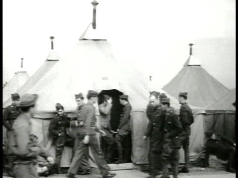 rows of military tents in army camp. soldiers standing by tents. int on beds inside tent. recruits marching. sergeant inspecting soldiers. wwii... - army stock-videos und b-roll-filmmaterial