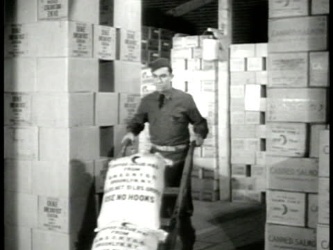 rows of military trucks parked. int workers moving supply boxes in warehouse w/ hand truck & dollies. sorting carrying boxes. wwii - warehouse点の映像素材/bロール