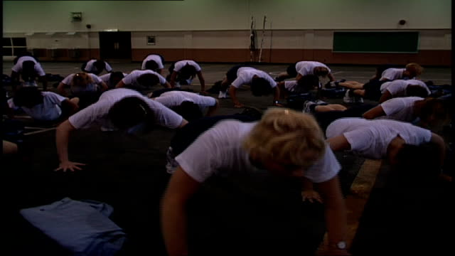 rows of navy rotc recruits doing push ups and jump ups in orlando, florida - allarme di prova video stock e b–roll