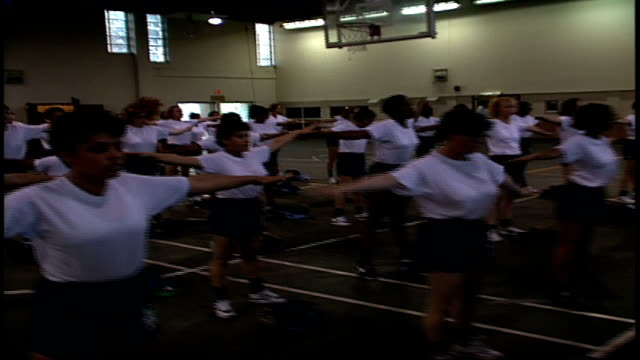 stockvideo's en b-roll-footage met rows of navy rotc recruits doing windmill toe touches in orlando, florida - vrijetijdsfaciliteiten