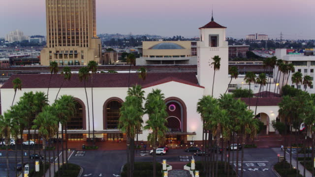 rows of palm trees outside union station, los angeles - drone shot with pan - union station los angeles stock videos & royalty-free footage