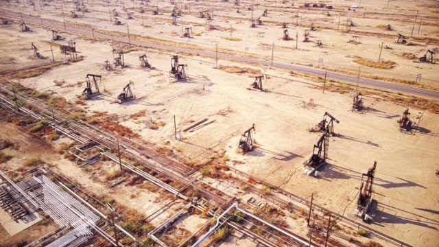 rows of pumpjacks in california oil field - industria petrolifera video stock e b–roll