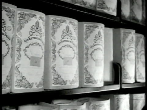 rows of shelves of records cu man pulling pack of files off shelf ms painting of pope leo xiii on wall 'rerum novarum' hanging on wall pamphlets fg... - anno 1943 video stock e b–roll