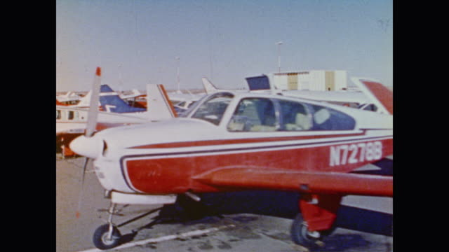 rows of small planes parked on an airfield - anno 1973 video stock e b–roll