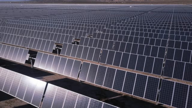vídeos de stock e filmes b-roll de rows of solar panels in vast power station - drone shot - gerador