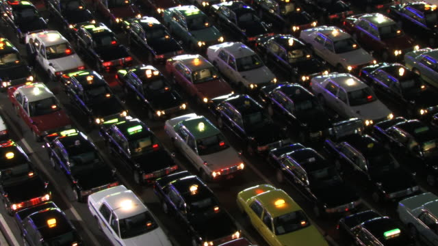 fast motion, ms, ha, rows of taxis in front of kyoto station at night, kyoto, japan - 豊富点の映像素材/bロール