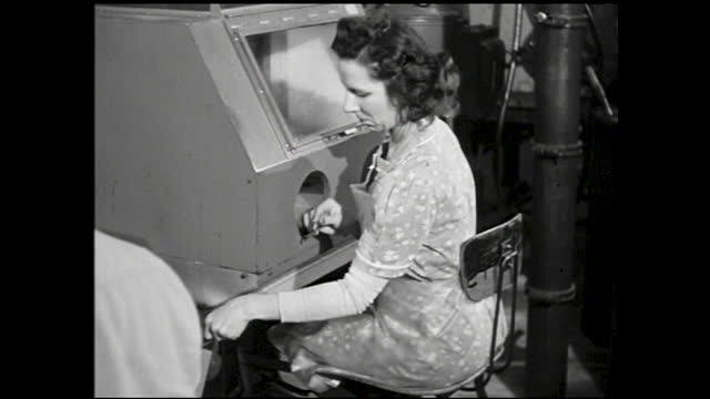 rows of telephone dials being spun and tested by machinery; panning view over table full of crystals; different views of workers working in front of... - 1940 1949 stock-videos und b-roll-filmmaterial