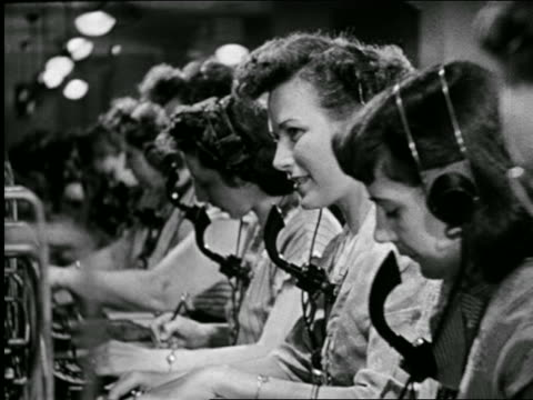 vídeos de stock e filmes b-roll de b/w 1946 side view rows of telephone operators with headsets working at switchboard / industrial - 1946