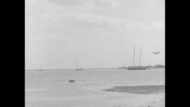 vidéos et rushes de pan right rows of whiskey barrels man counting them/ men moving boxes from one place to another / lspan left boats with sails down / aerial of island... - bahamas