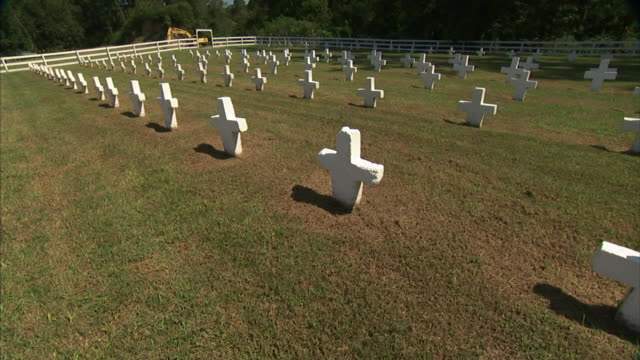 Rows of white Christian cross headstone grave markers in wooden fenced area woods BG PAN Prison graveyard grounds Death interned buried impermanence