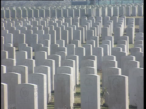 Rows of white headstones in cemetery zoom out to reveal hundreds more headstones Somme