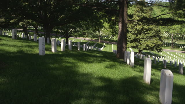 Rows of white headstones slanting down a shady hillside in Arlington National Cemetery. Shot in May 2012.