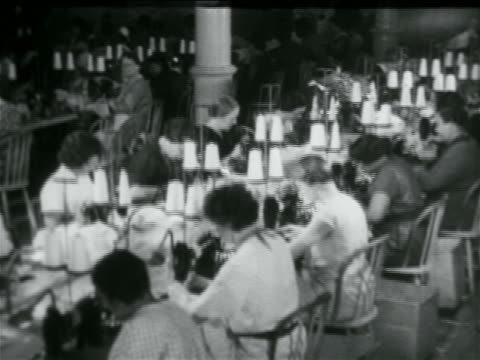 b/w 1934 rows of women using sewing machines in wpa garment factory / documentary - 1934 bildbanksvideor och videomaterial från bakom kulisserna