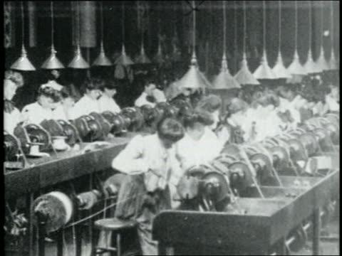 b/w 1904 rows of women work on machinery in textile? factory - 1900~1909年点の映像素材/bロール