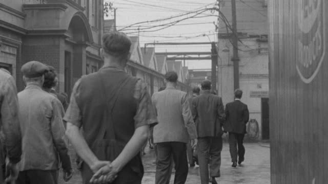 vidéos et rushes de 1957 montage rows of workers arriving at factory, placing bicycle on rack, punching time clock, and filing off to their jobs / united kingdom - 1957