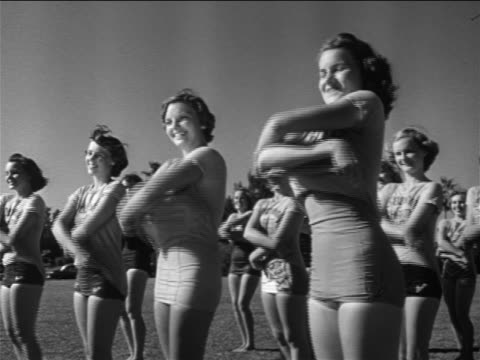 B/W 1951 rows of young women in bathing suits standing on grass removing t-shirts / St. Petersburg