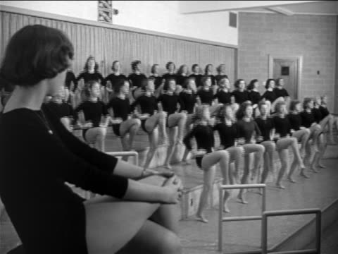 b/w 1953 rows of young women in black leotards practicing dance kicks / documentary - gymnastikanzug stock-videos und b-roll-filmmaterial