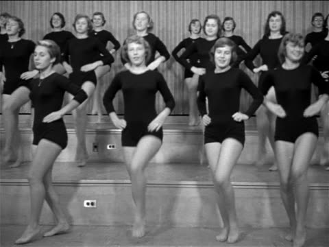 b/w 1953 rows of young women in black leotards practicing dance kicks / documentary - 1953 stock videos and b-roll footage
