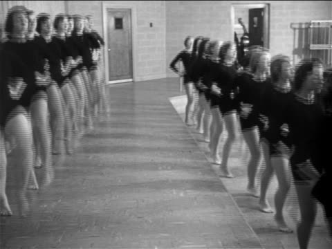 b/w 1953 pan rows of young women in black leotards practicing dance kicks / documentary - gymnastikanzug stock-videos und b-roll-filmmaterial