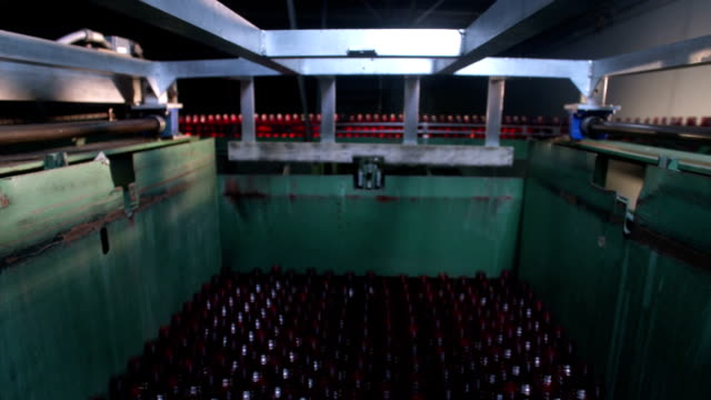 rows & rows of red unmarked uncapped glass bottles on platform rising up into & toward frame fg, bottles moving on conveyor belt behind glass bg.... - moving up点の映像素材/bロール