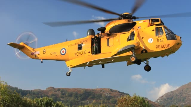 royal air force sea king helicopter attending a mountain rescue incident in ambleside in the lake district, uk. - hovering stock videos & royalty-free footage