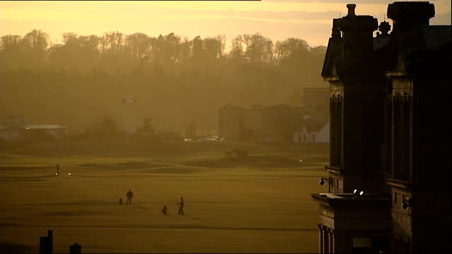 stockvideo's en b-roll-footage met royal and ancient golf club votes in favour of allowing women members; t26031410 - 26.3.2014 golfers on golf course and club at sunset - atlete