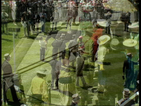 vídeos de stock e filmes b-roll de royal ascot 15 elevated views of people milling around chatting etc people behind barrier waiting for royal procession woman taken off in wheelchair... - 1980 1989