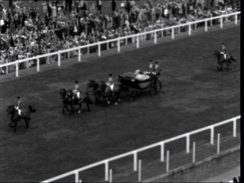 first day:; england: berkshire: ascot: ext carriage along carrying queen elizabeth ii and prince philip, duke of edinburgh gvs royal drive queen and... - イギリス アスコット競馬場点の映像素材/bロール