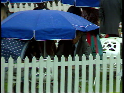 ENGLAND Ascot Two women wearing seethrough plastic macs over their dresses huddle under umbrella PULL OUT large group of women huddled under...