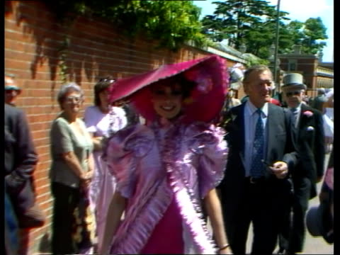 berkshire: ascot: ext crowds in enclosure two women in pretty dresses and hats woman with large hat and man in top hat and tails two women walk along... - berkshire england stock videos & royalty-free footage