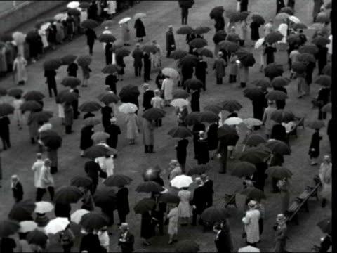second day:; england: berkshire: ascot racecourse: gvs crowds with umbrellas - イギリス アスコット競馬場点の映像素材/bロール