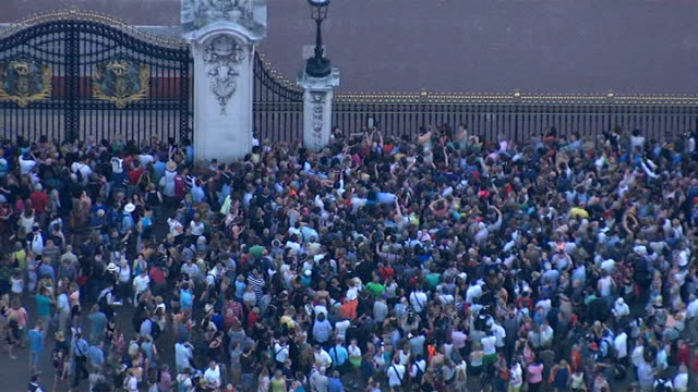 aerials of crowds outside buckingham palace england london buckingham palace buckingham palace / crowd outside gates of buckingham palace / bt tower... - bt tower london stock videos & royalty-free footage