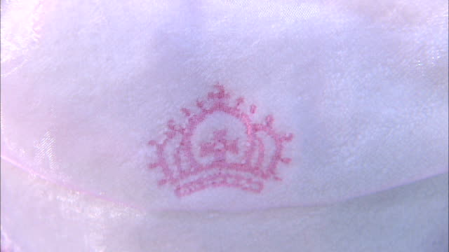 economic impact location unknown close shot 'hrh princess alexandra' stitched on clothing close shots of embroidered crown london reporter to camera... - baby clothing stock videos & royalty-free footage