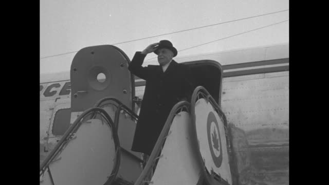 Royal Canadian Air Force jet approaches as it taxis on snowy airfield / Canadian Prime Minister Louis St Laurent waves his hat as he stands at top of...