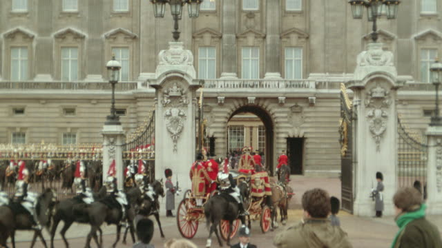 REAR VIEW royal carriages followed by mounted guards entering gates of Buckingham Palace / London