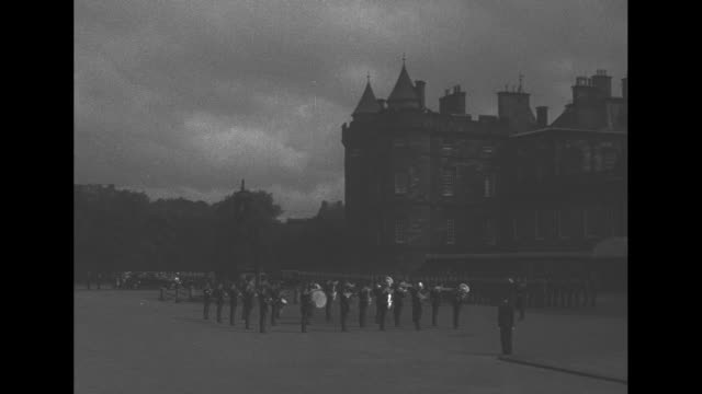 royal cars proceed down princess street as throngs of people line curb on either side/ cu car passes/ people gathered/ ws marching band outside of... - holyrood bildbanksvideor och videomaterial från bakom kulisserna