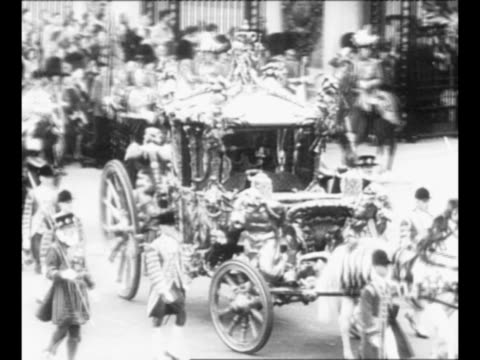ws royal coach and procession move through crowds proceeding from buckingham palace toward westminster abbey site of queen elizabeth's coronation... - フットマン点の映像素材/bロール