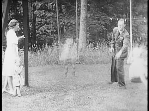 royal family exits their house / the parents put the children in the swimming pool / the parents push the children in a swing as a newsreel cameraman... - newsreel stock videos and b-roll footage