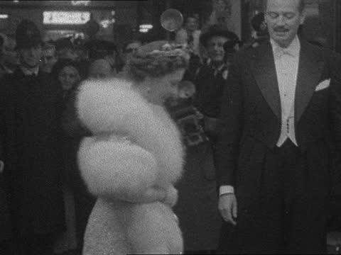 royal film performance: 'les girls'; england: london: leicester square: ext / night gv ext odeon: sophia loren waves jack hawkins waves: jayne... - sophia loren stock videos & royalty-free footage