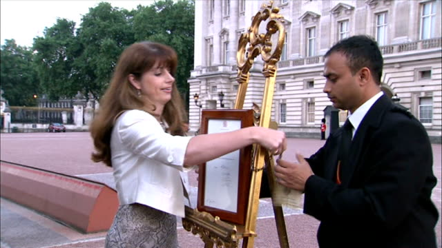 royal footman returns to india after is visa runs out file / 2372013 ext ailsa anderson and badar azim fixing royal proclamation to gold easel - easel stock videos and b-roll footage