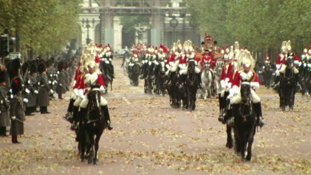 royal guards riding horses toward camera in front of royal carriage / london, england - 騎兵隊点の映像素材/bロール