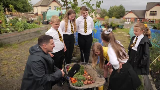 royal horticultural society to announce winners of first community garden awards; scotland: glasgow: lochend community garden: ext girl watering soil... - royal horticultural society stock videos & royalty-free footage