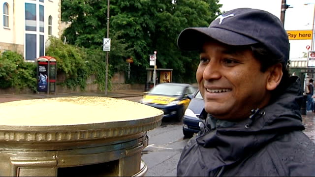 royal mail pledges to paint a red post box gold in the home town of every british olympic champion.; man taking photograph of man posing by post box... - top of the pops stock videos & royalty-free footage