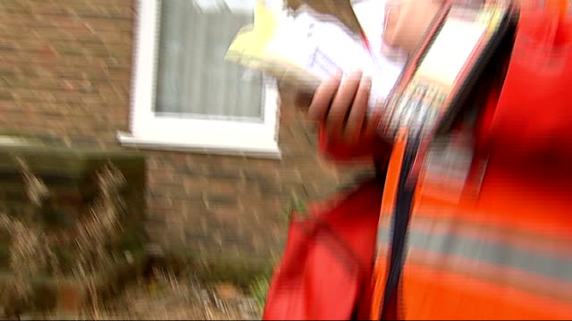 postal worker delivering mail england london bow ext vincent micallef delivering post to house / tracking shot following micallef on round / micallef... - postman stock videos and b-roll footage