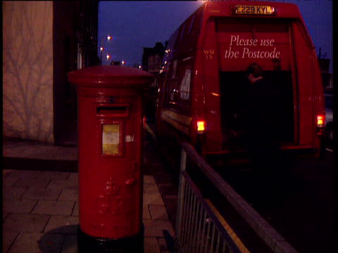 vidéos et rushes de royal mail postal worker leaves parked van and collects mail from red post box - facteur