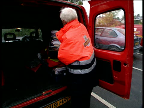 royal mail postal worker puts box of sorted mail into back of van - postal worker stock videos & royalty-free footage