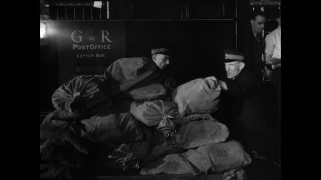 MONTAGE Royal Mail postal workers unloading and loading sacks of mail from Holyhead onto another train, postal train pulling out of the Stafford station while workers are waving good-bye / England, United Kingdom