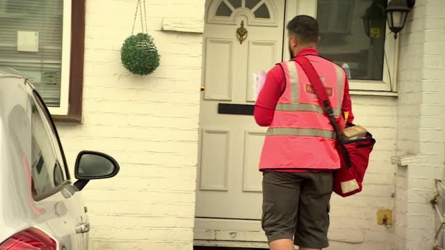 royal mail postman delivering parcel observing social distancing rules during lockdown during coronavirus crisis, london - ロイヤルメール点の映像素材/bロール