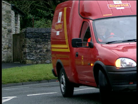 stockvideo's en b-roll-footage met royal mail van turns onto road and parks outside village post office - post