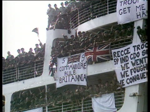 royal marine commandos lining decks of canberra sing 'rule britannia' as ship approaches dock on return from falklands conflict southampton 11 jul 82 - 英国ハンプシャー点の映像素材/bロール